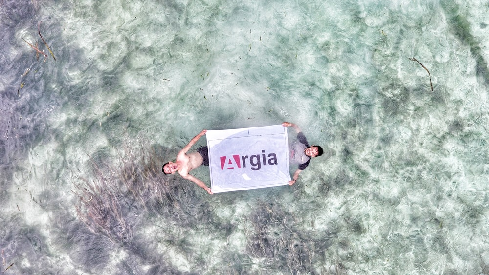 aerial view photo of two person holding Argia flag