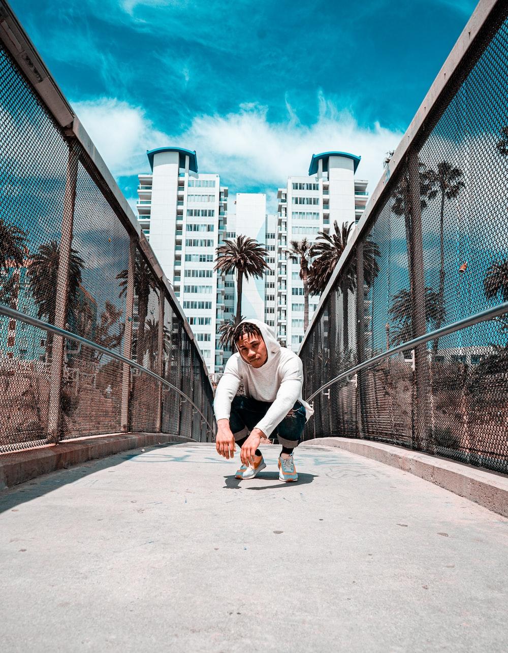 man squat sitting on bridge