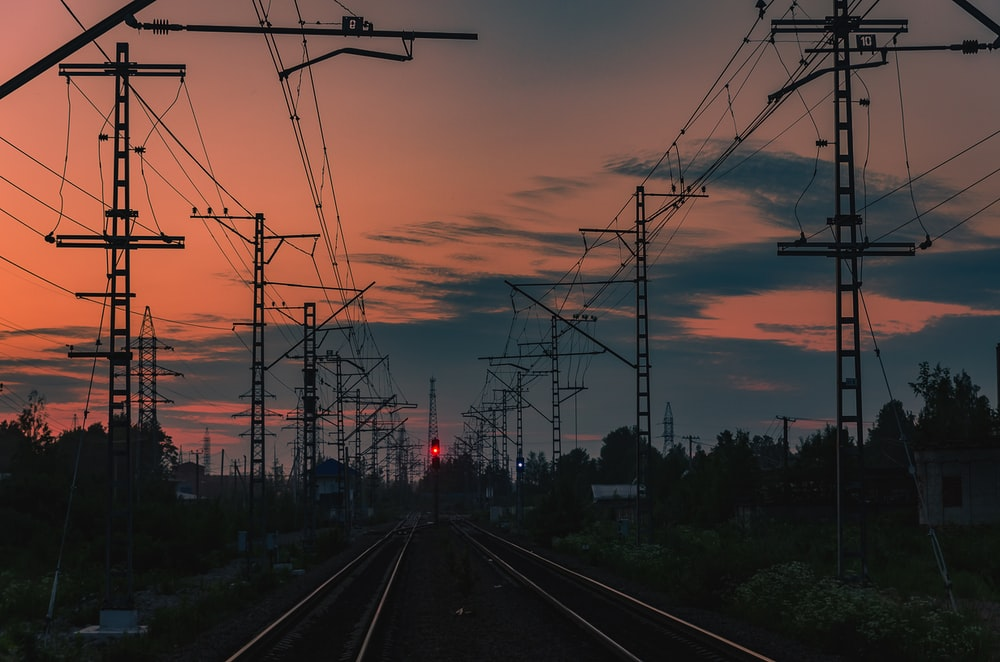 landscape photo of train tracks lined with electric towers