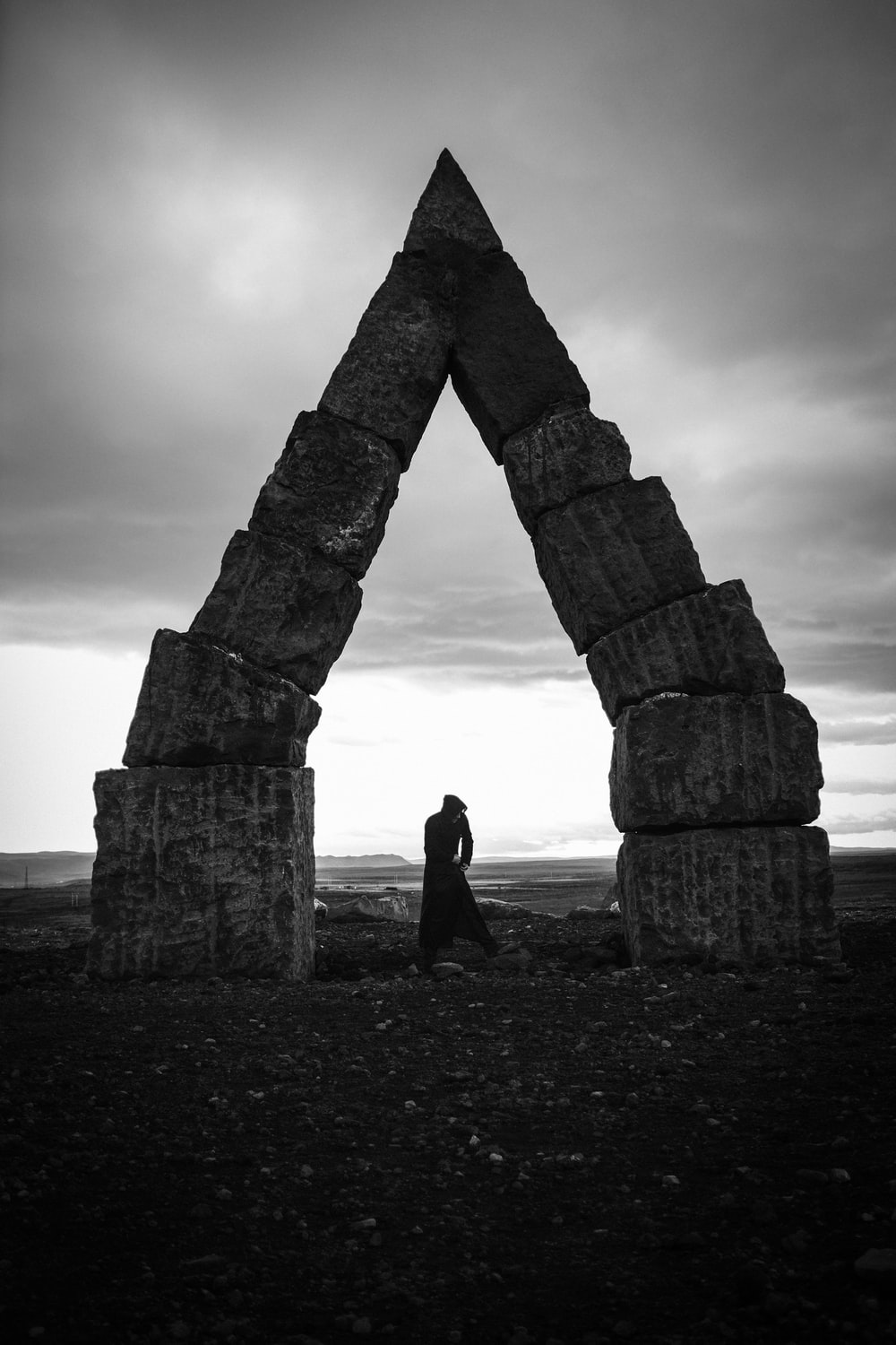 grayscale photography of person standing near arch decor