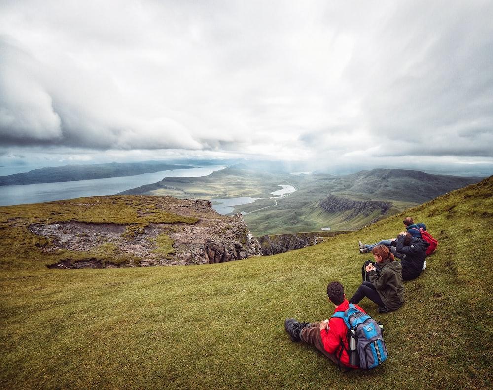 three person sitting on green mountain