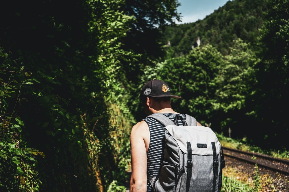 shallow focus photo of man wearing black flat brim cap and gray backpack