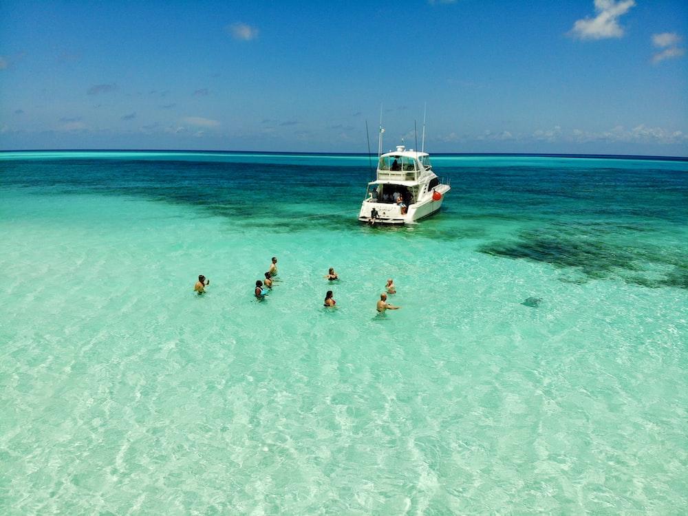 people on body of water in Cozumel across white yacht