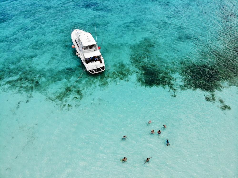 bird's-eye photography of people near white boat