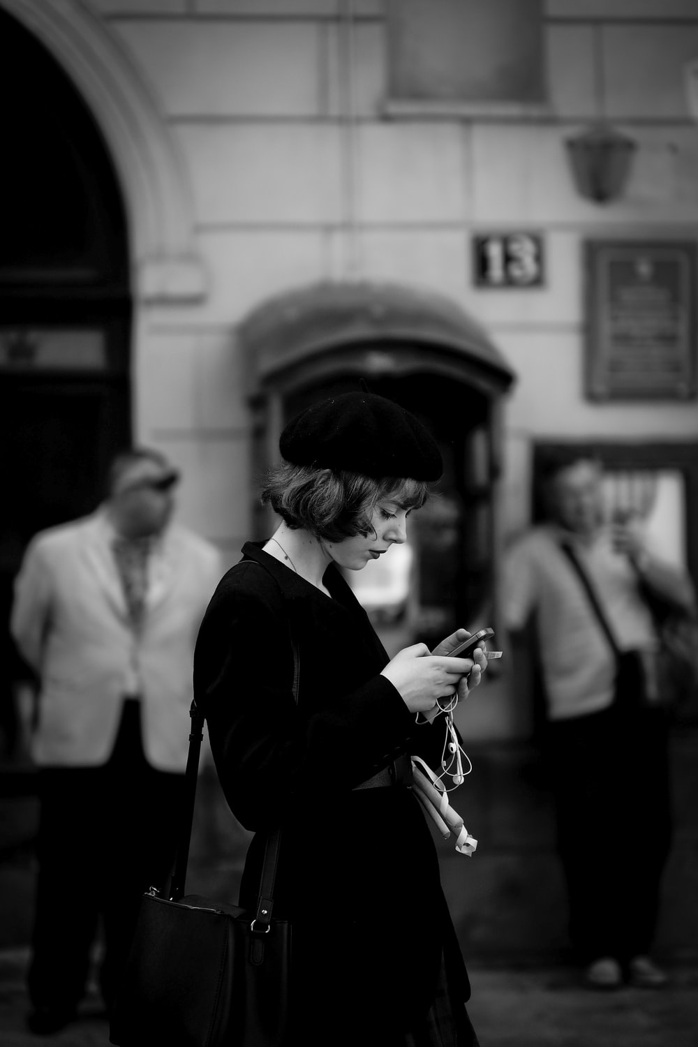 grayscale photo of woman using smartphone