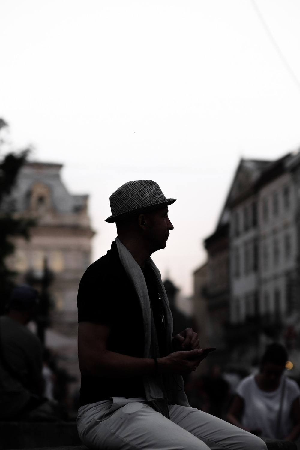 silhouette of sitting man next to person who wearing white shirt during daytime