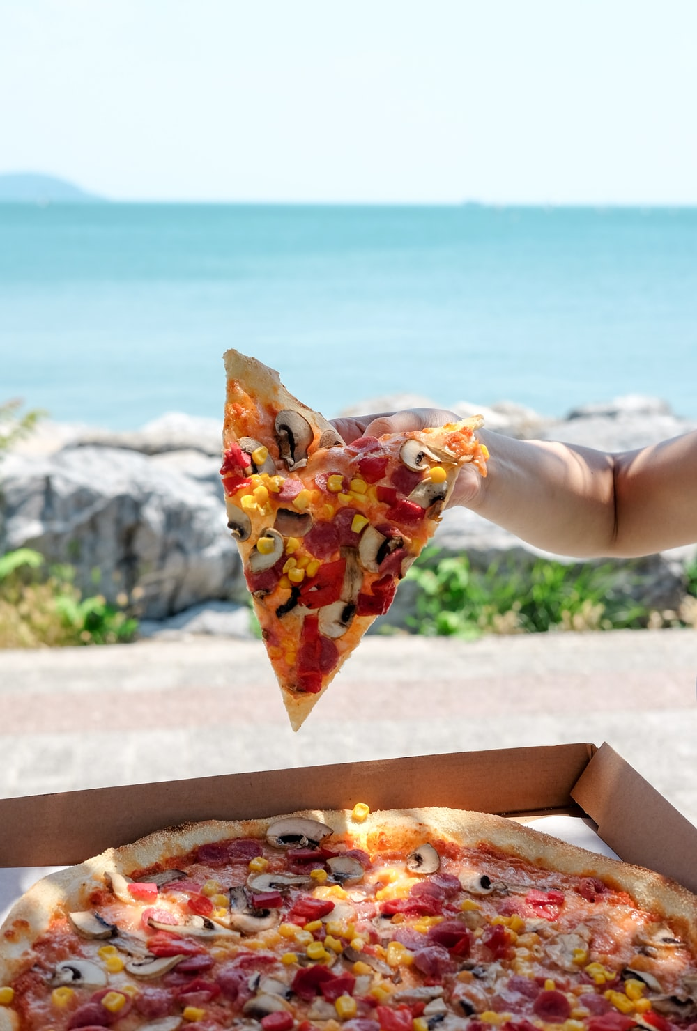person holding slice of pizza