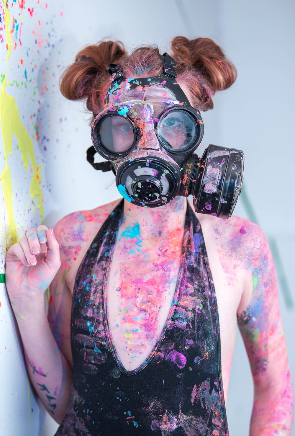 multicolored paint splattered woman wearing black monokini and gas mask standing beside wall