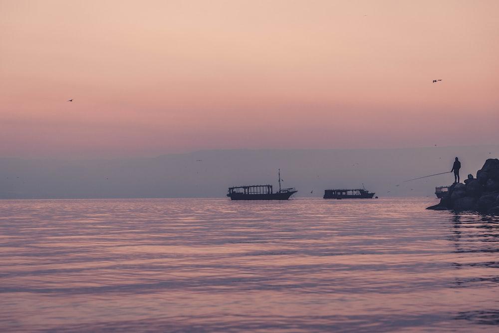 man fishing near two boats
