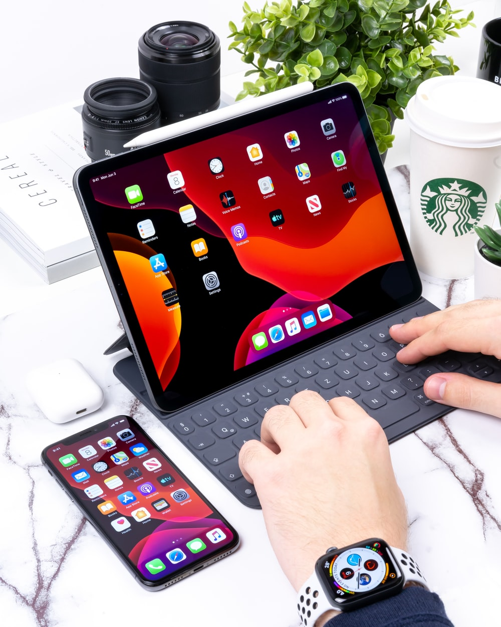 person typing on grey bluetooth keyboard for black Apple iPad