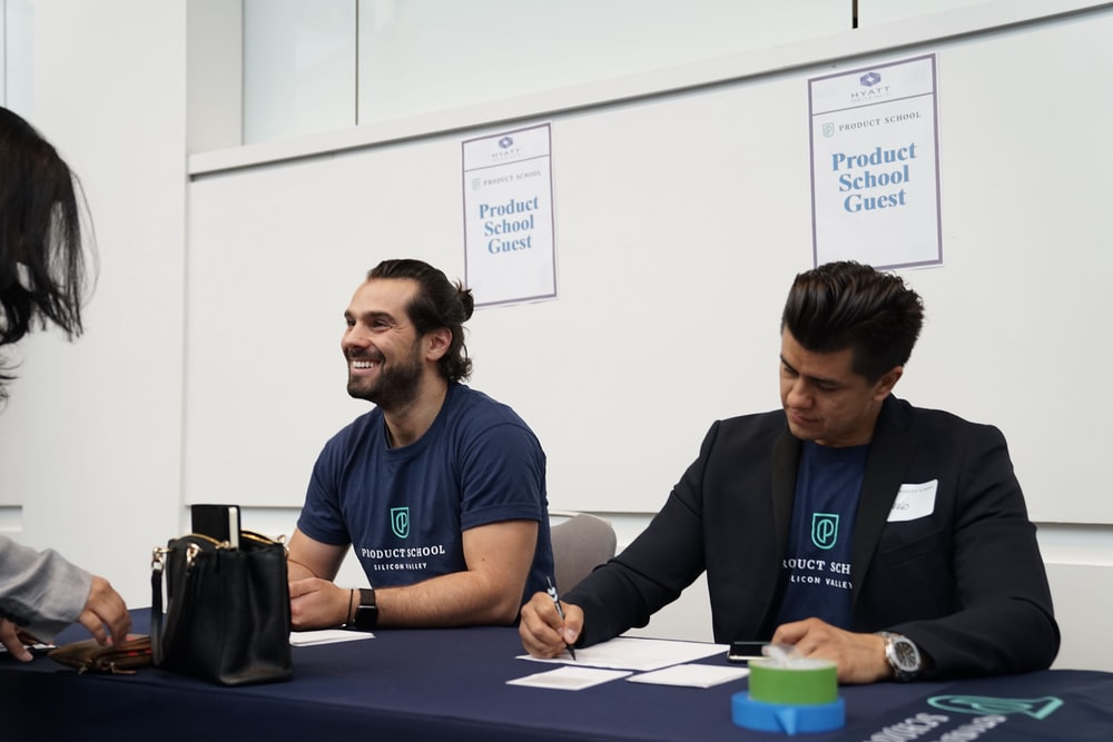 two men sitting on blue tables