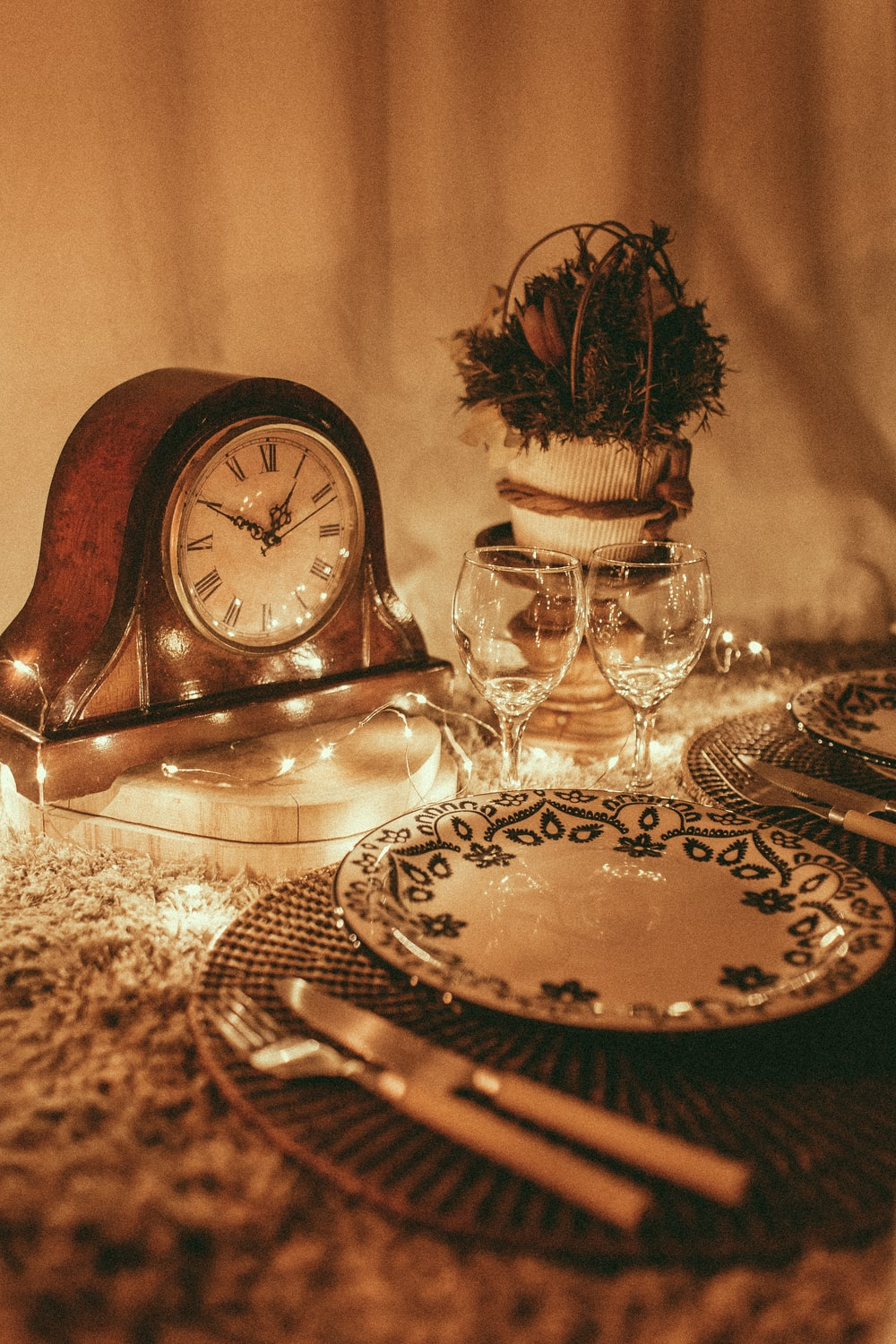 empty white plate near wine glasses and anniversary clock displaying 1:50