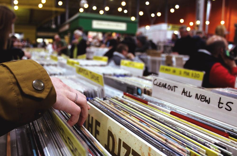 person in brown jacket selecting vinyl sleeves