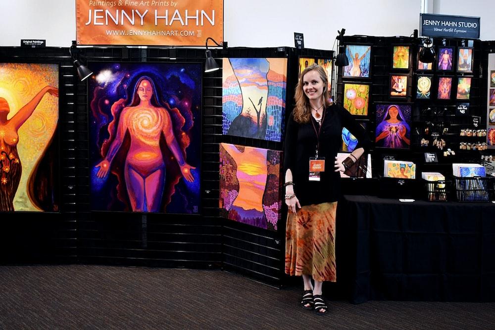 woman standing beside paintings