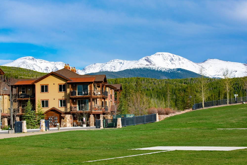 brown house near grass field with view of snow mountain during daytime