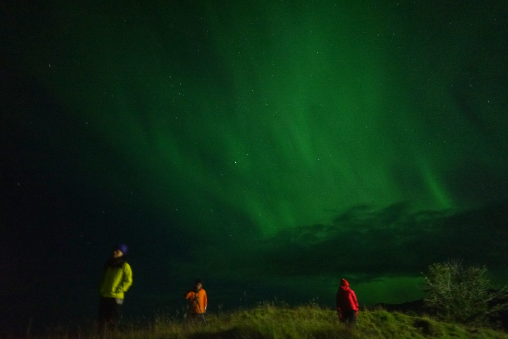 northern lights photography of three men on mountain