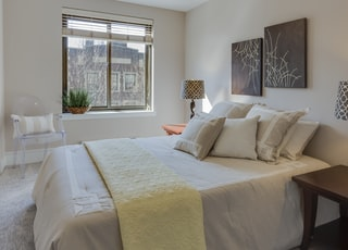 bed with comforter set beside table lamps on nightstands