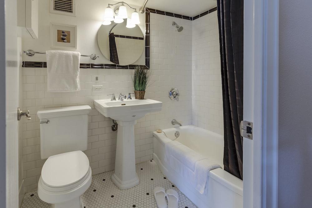 white ceramic toilet bowl beside pedestal sink