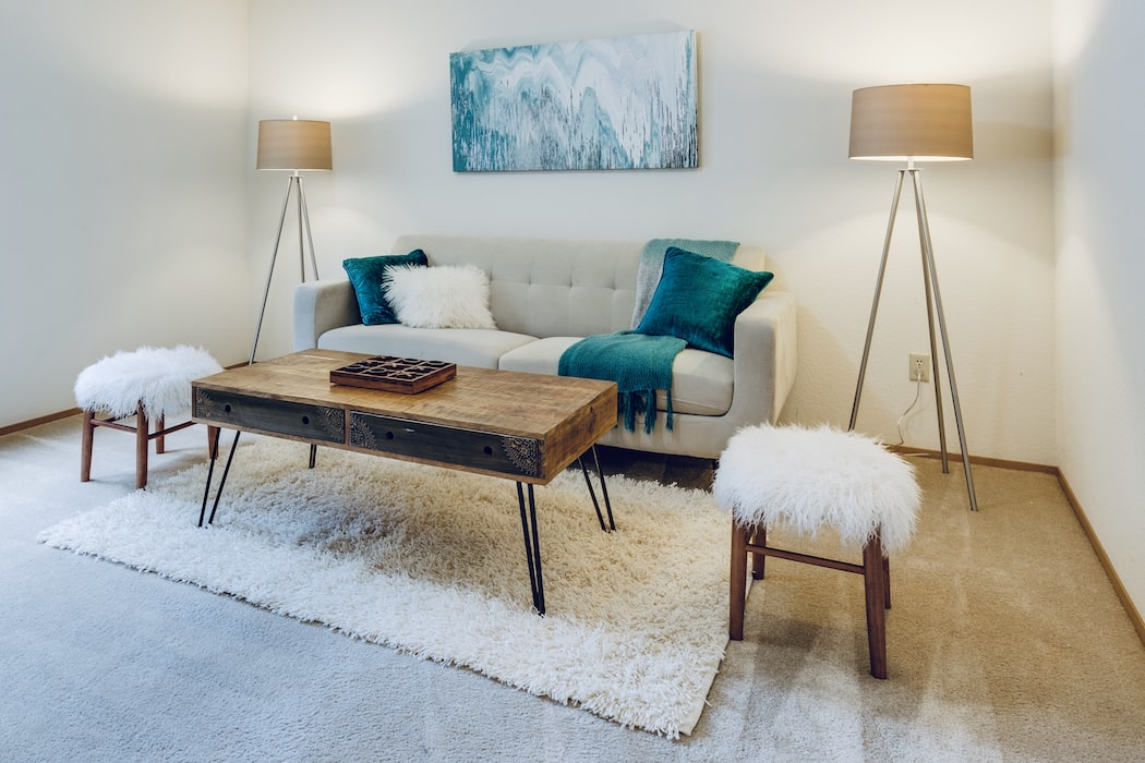 A living room with a grey sofa, wooden coffee table, and blue wall art