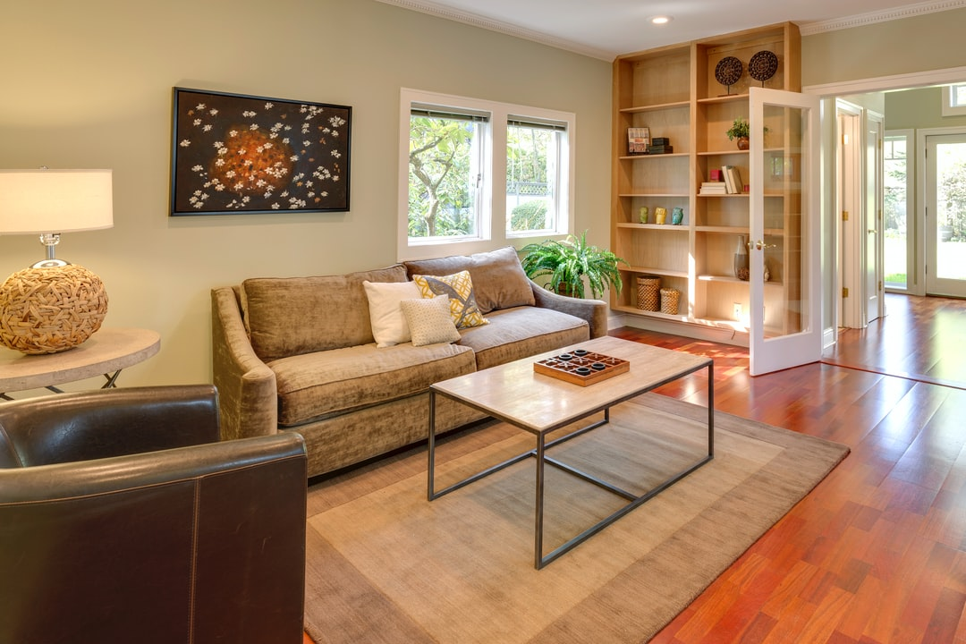 brown wooden table and couch with brown wooden bookshelf