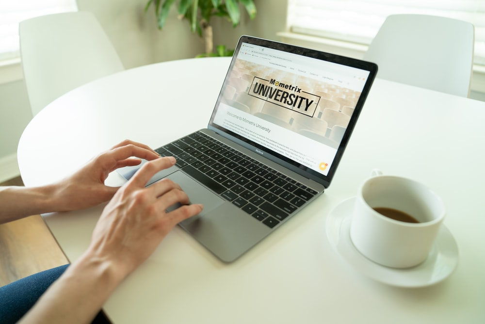 black and gray laptop beside teacup