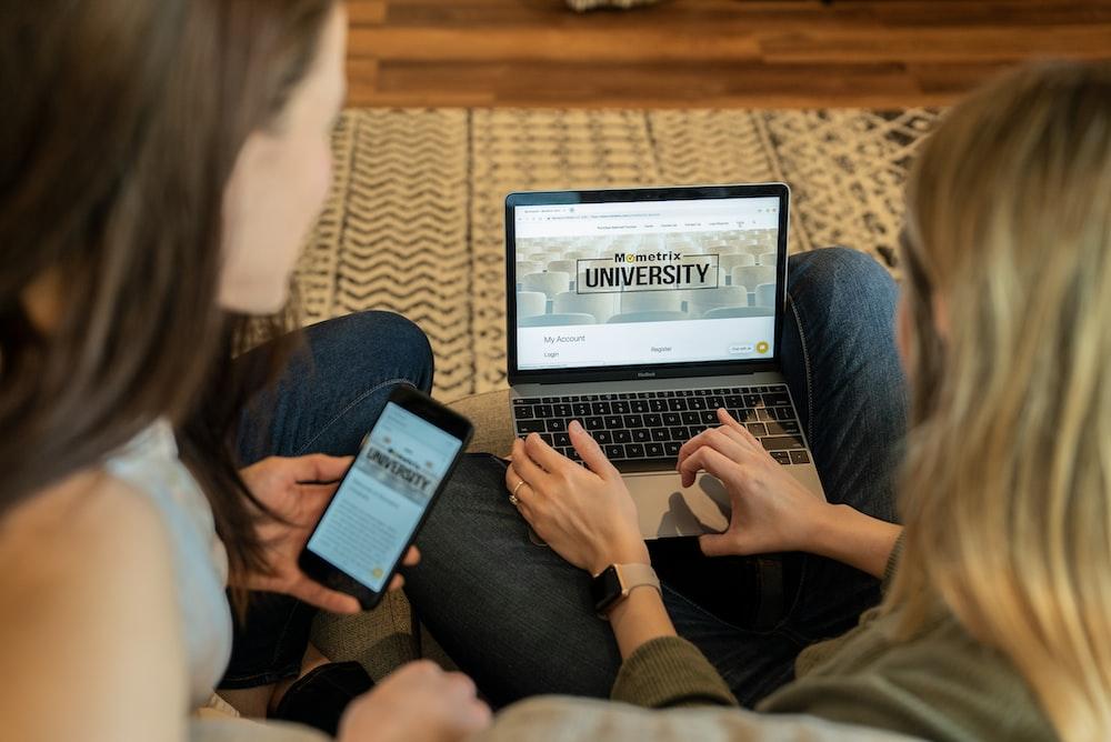 woman using laptop sitting beside woman holding smartphone