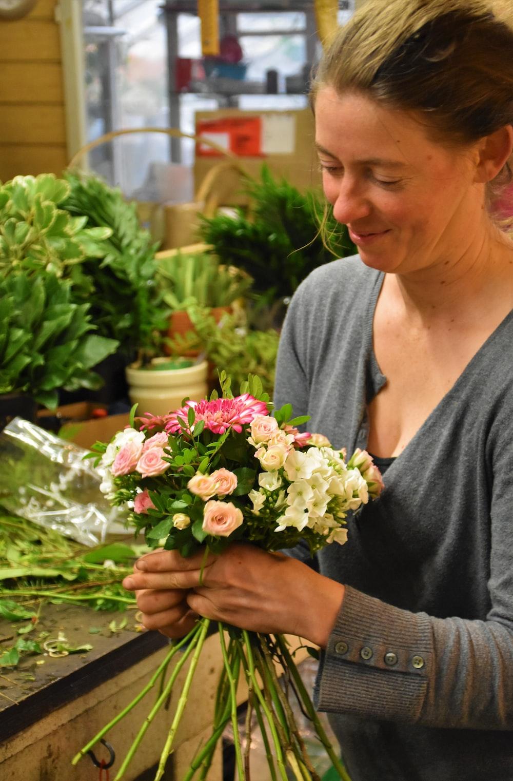 woman wearing gray cardigan holding flower bouquet