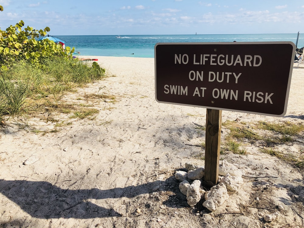 brown and white No lifeguard on duty signage