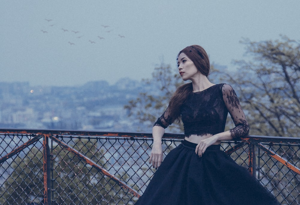woman wearing black laced ballgown standing beside black mesh-link fence