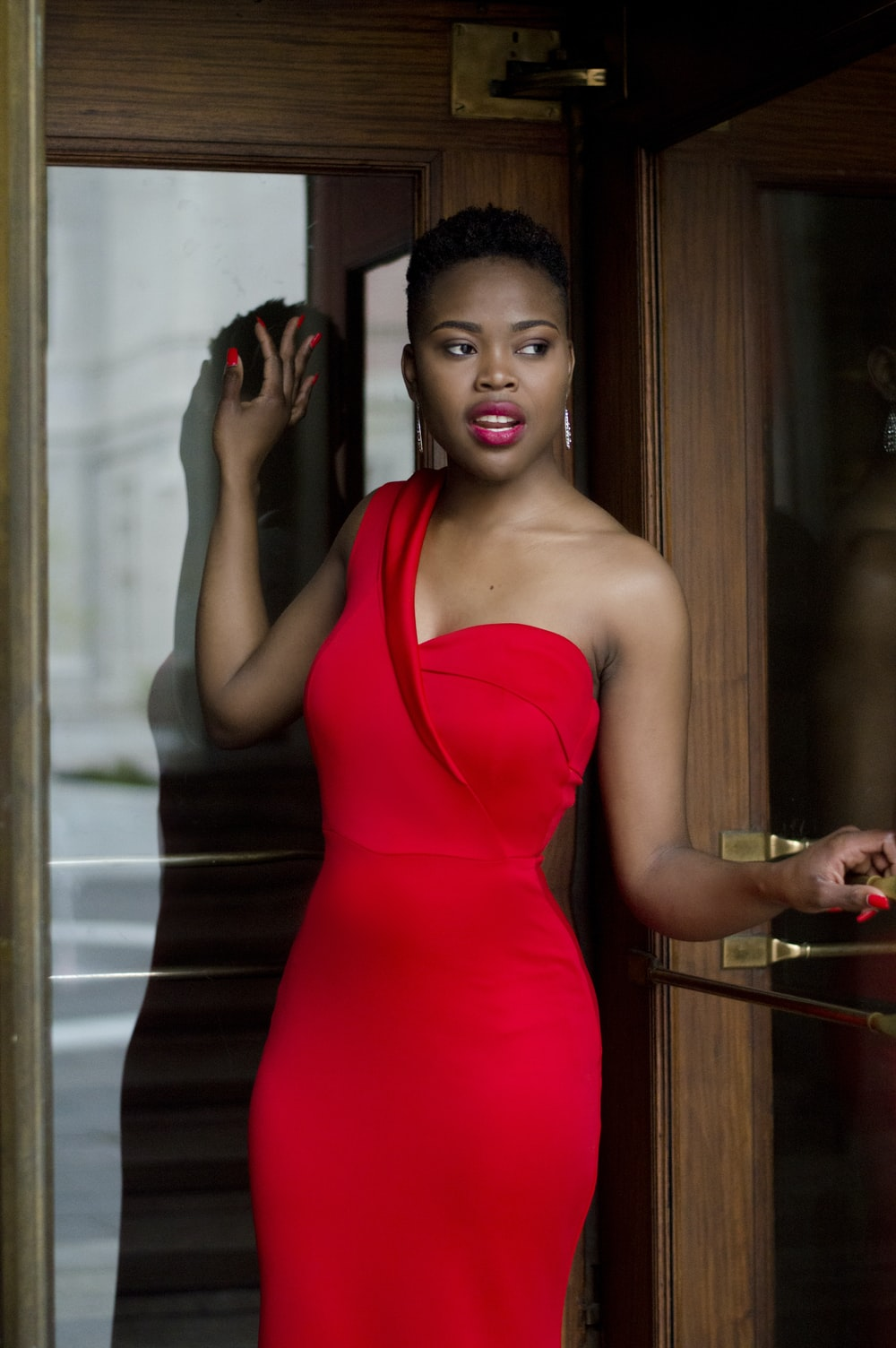woman wearing red bodycon dress holding glass door