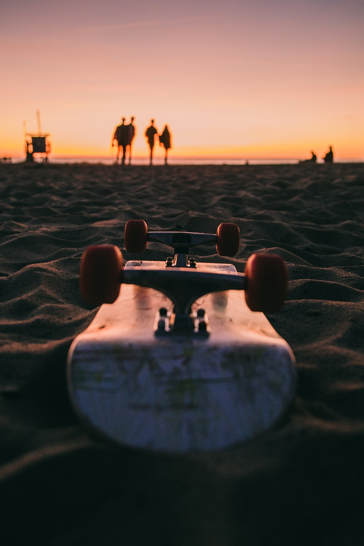 close-up photography of skateboard on beach sand