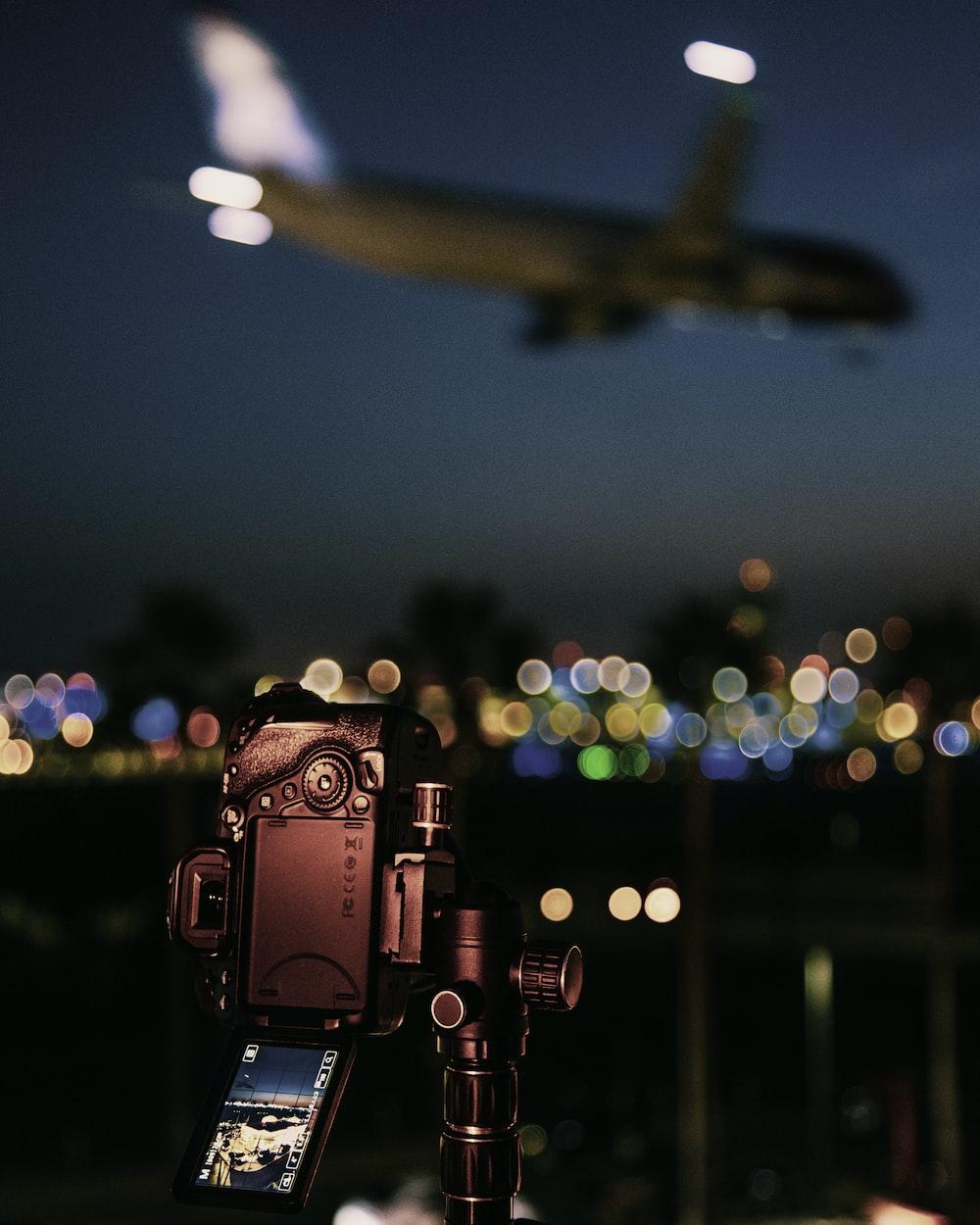 black video camera capturing an airplane in flight