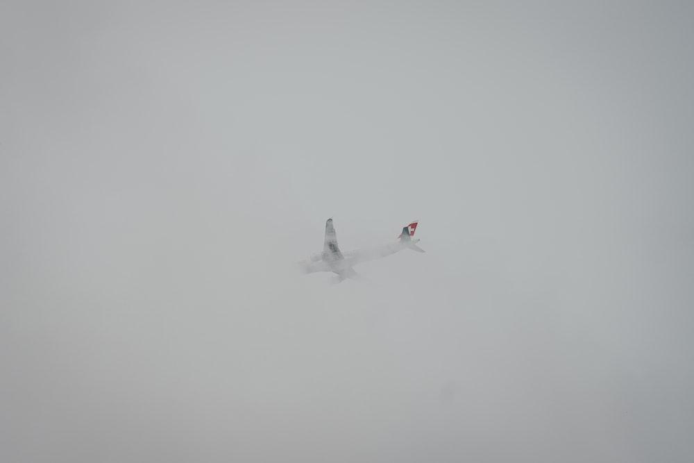 white airliner flying on sky covered fog