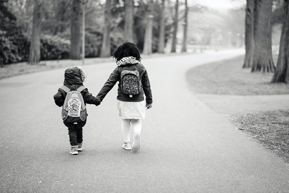 grayscale photography of two toddlers walking on road