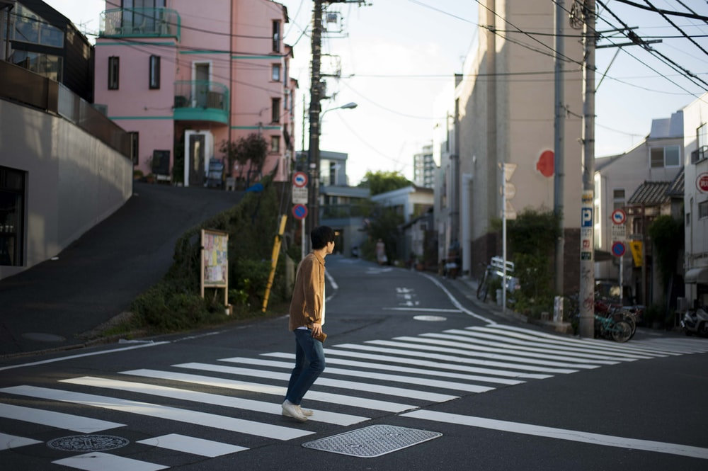 person crossing pedestrian lane during daytime