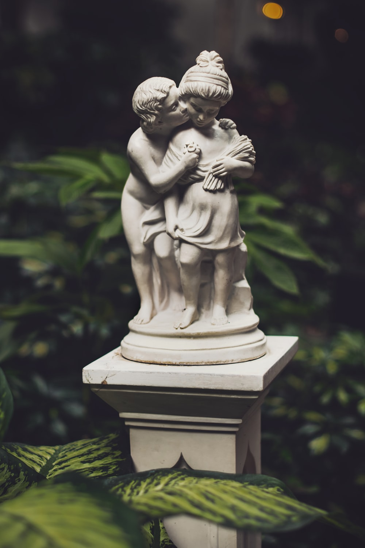 boy kissing girl statuette