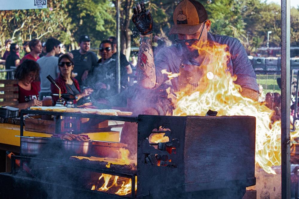 man in cap standing near grill