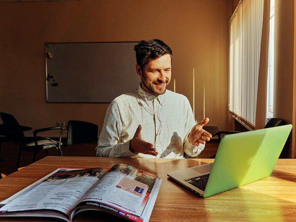smiling man facing laptop