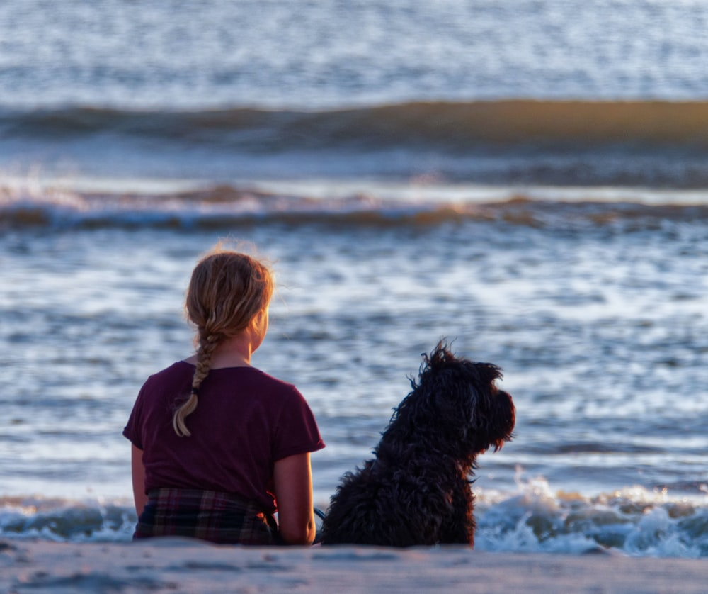 girl and dog sitting on seashore while watching on sea