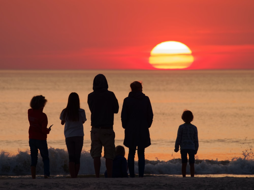 silhouette photography of people facing ocean during golden hour