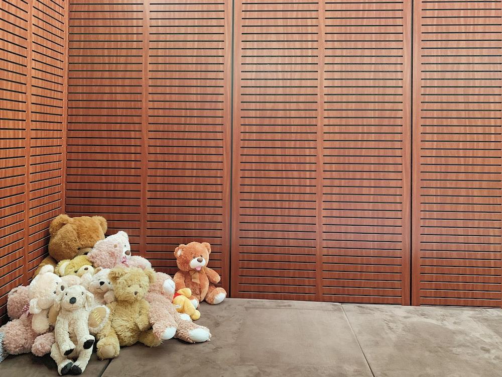 pile bear plush toys beside wall