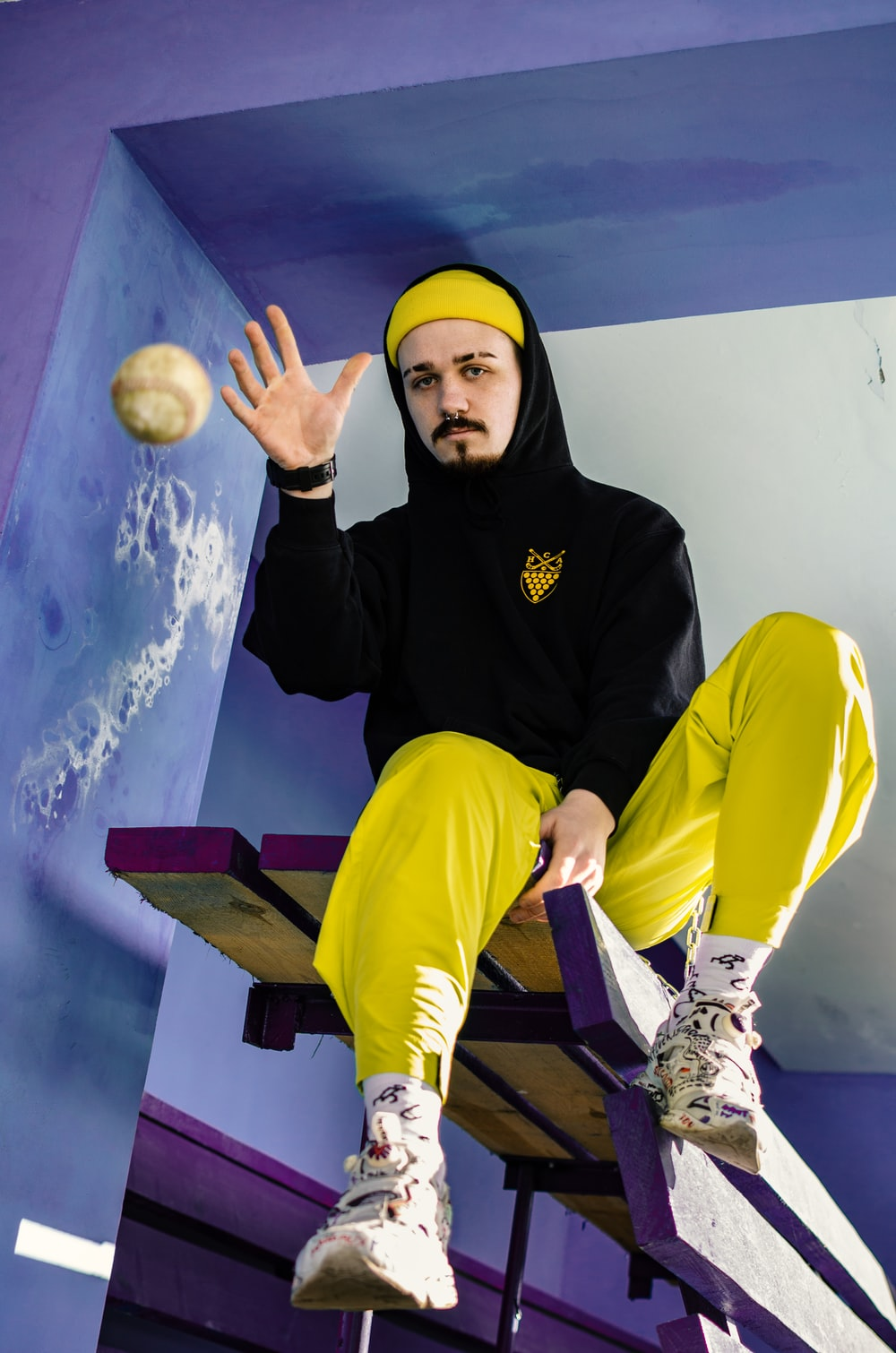 man wearing yellow pants and black hoodie about to throw the tennis ball