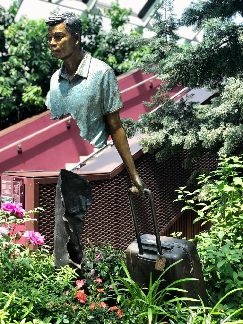 man pulling luggage statue