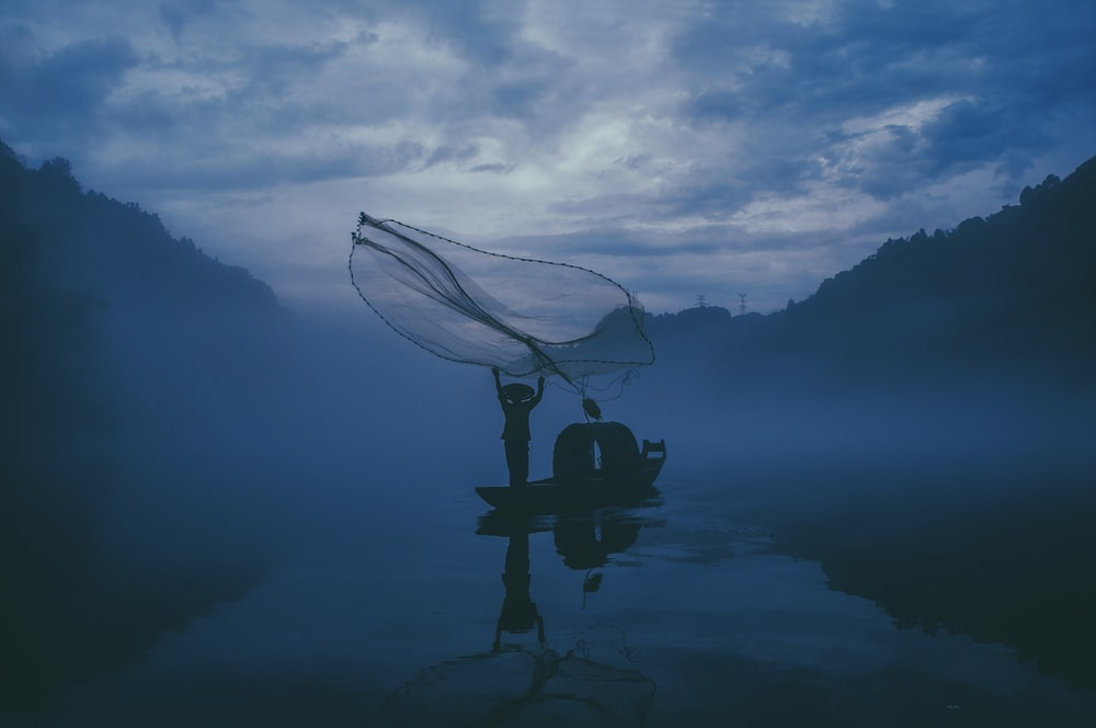 person fishing in a body of water during nightime