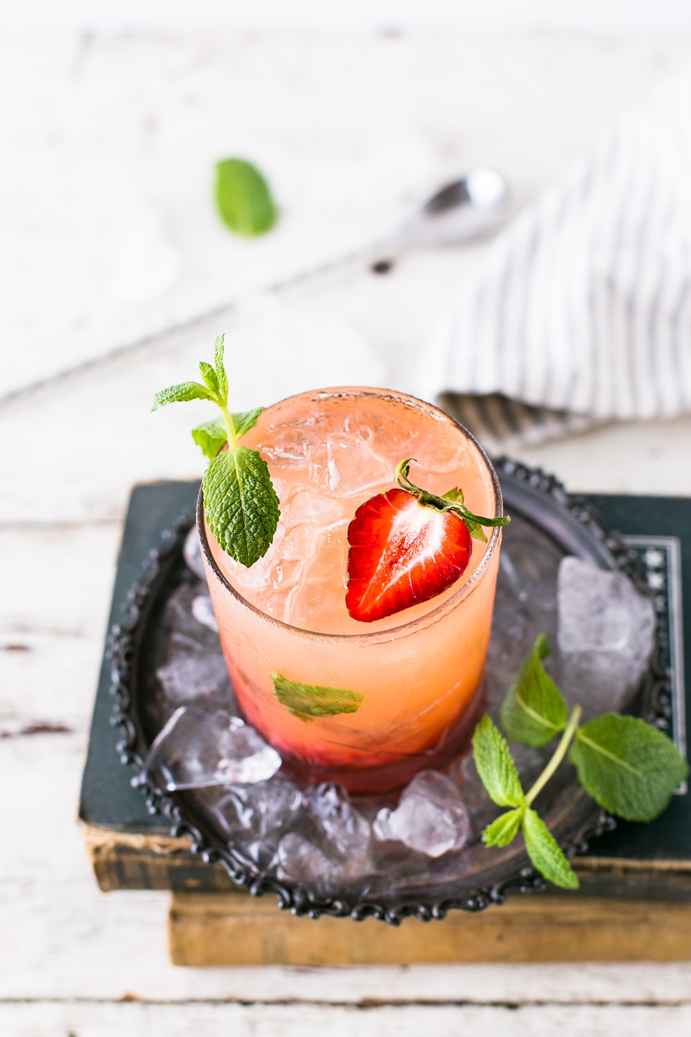 clear glass cup with red beverage and strawberries