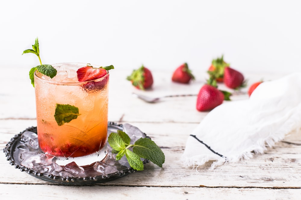 glass of mint and strawberry beverage on brown panel