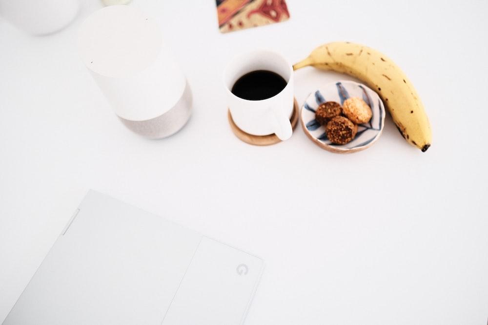 white ceramic mug beside yellow banana flower