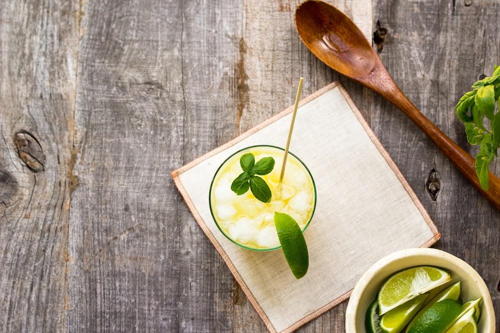 juice in cup on board beside wooden spoon