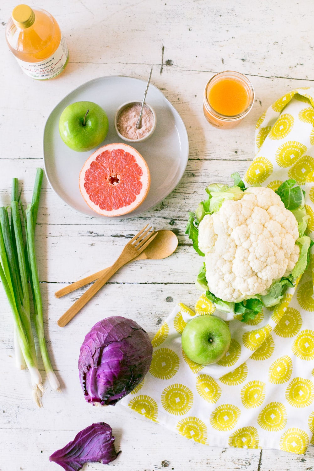 green apple, sliced of grapefruit with purple cabbage, scallions and cauliflower on table