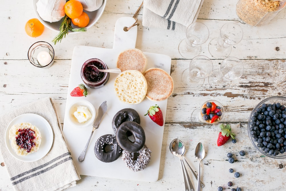 flat lay photography of breakfast with berries and doughnuts